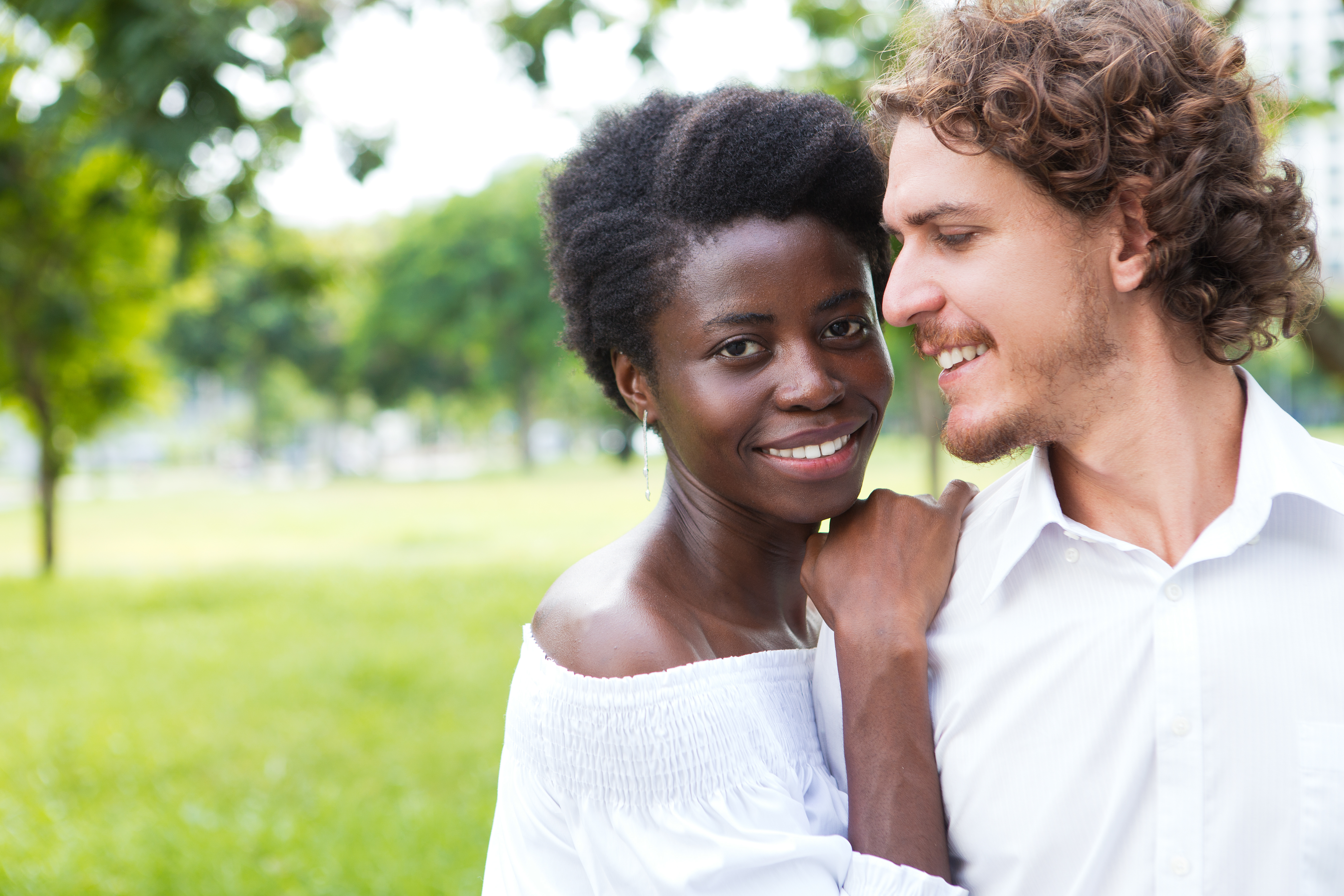 happy-young-man-looking-his-girlfriend-outdoors, biracial couple, happy couple smiling black and white